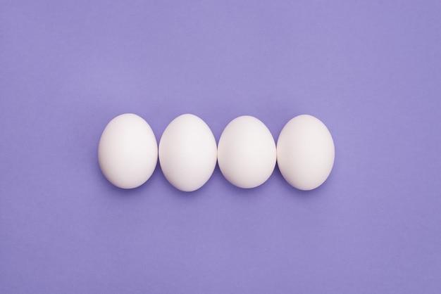 Zamknij się zdjęcie widoku z góry narzutu czterech jaj w rzędzie z białej skorupy na białym tle fioletowy kolor tła