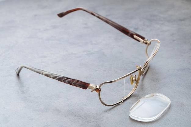 Zamknij się zepsute okulary z uszkodzoną ramką i soczewką leżącą na stole w sklepie optycznym