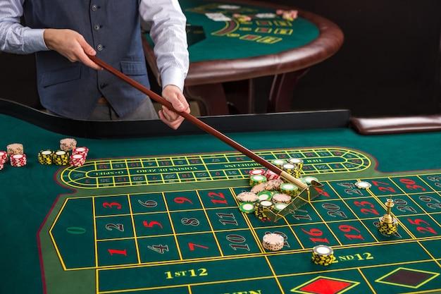 Zamknij się żetony do gry na zielonym stole w kasynie. krupier zbiera żetony za pomocą patyka