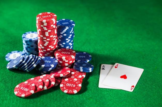 Zamknij się żetony w kasynie i dwie karty ace na zielonym stole