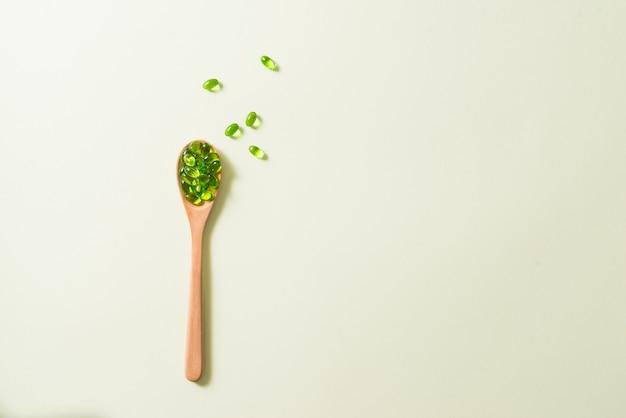Zamknij się zielone kapsułki softgel z drewnianą łyżką na na białym tle.