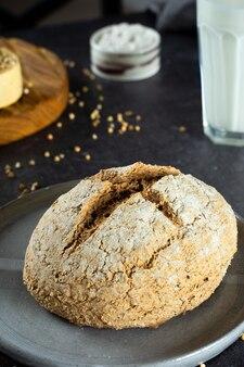 Zamknij się zielony chleb gryczany i ekologiczne mleko gryczane. szary domowy talerz ceramiczny, lniana serwetka. nieszkodliwe, zdrowe, bezglutenowe zdrowe wypieki dla wegan. alternatywny chleb i mleko wegetariańskie