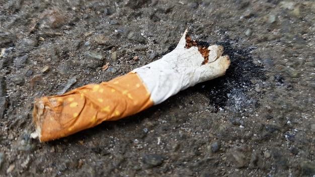 Zamknij się złamany niedopałek na asfalcie z miejsca na kopię. międzynarodowy dzień bez tytoniu. światowy dzień walki z papierosami, nikotyną i tytoniem.