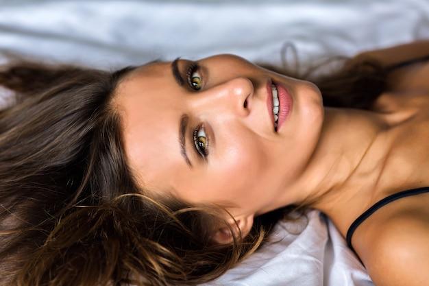 Zamknij się zmysłowy portret pięknej, pięknej brunetki kobiety z niesamowitą zieloną oliwką tak, porannym miękkim światłem, naturalnym pięknem, spa i koncepcją pielęgnacji skóry.