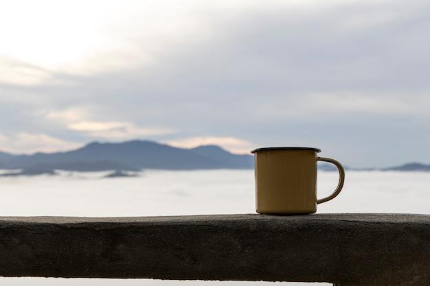 Zamknij się żółty blaszany kubek gorącej kawy z mgłą na tle góry rano.