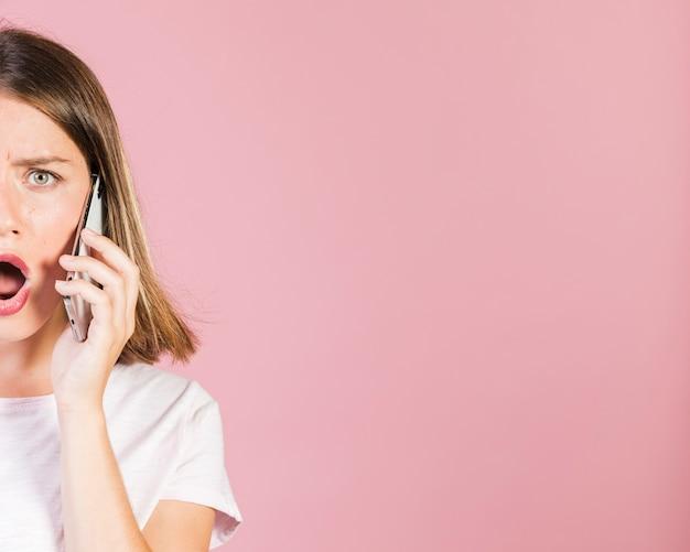 Zamknij się zszokowana dziewczyna jest w telefonie