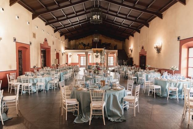 Zamknij - skonfiguruj. elegancka, przytulna i stylowa sala konferencyjna. ustawienia stołu na przyjęciu weselnym. kompozycje kwiatowe z pięknymi kwiatami, świecami i luksusowymi sztućcami na ozdobionym stole.
