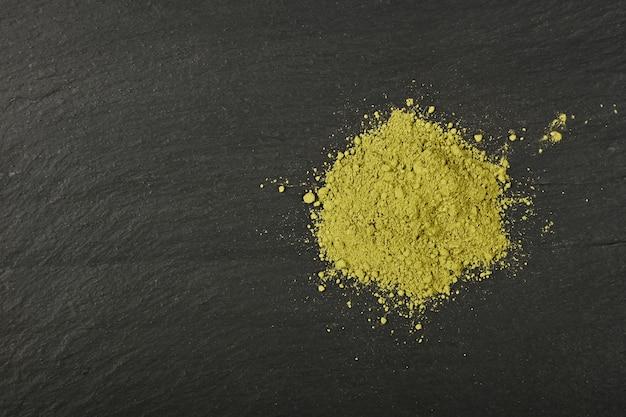 Zamknij stertę pełną zmielonej nieprażonej surowej zielonej kawy arabica na tle czarnej tablicy łupkowej, podwyższony widok z góry, bezpośrednio nad