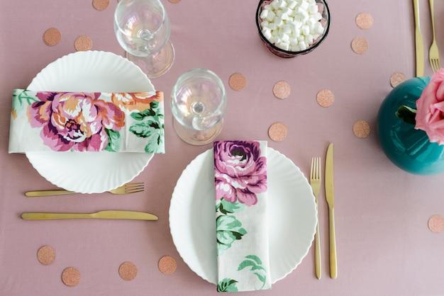 Zamknij stół urodzinowy lub weselny w kolorze różowym i kolorach z serwetkami, złotymi sztućcami, różą w wazonie. baby shower lub party girl. widok z góry