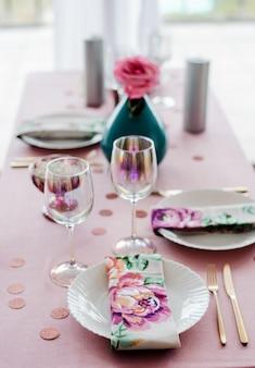 Zamknij stół urodzinowy lub weselny w kolorze różowym i kolorach z serwetkami, złotymi sztućcami, różą w wazonie. baby shower lub party girl.