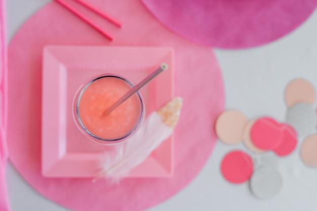 Zamknij stół urodzinowy lub weselny w kolorze różowym i kolorystycznym z napojami, szklanką koktajlu. baby shower lub party girl. widok z góry