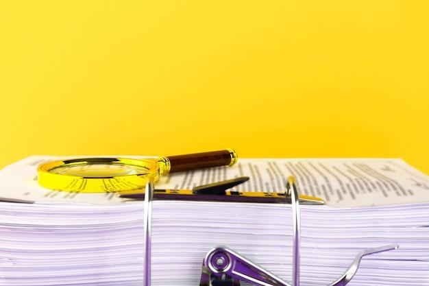 Zamknij stos niedokończonych dokumentów oczekujących na weryfikację, szkło powiększające, na żółtym tle. koncepcja biznesu i edukacji. skopiuj miejsce