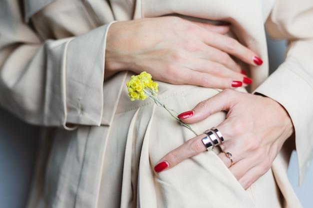 Zamknij strzał kobieta ręce czerwony manicure dwa pierścienie na sobie beżowy garnitur. żółty ładny suszony kwiat w kieszeni.