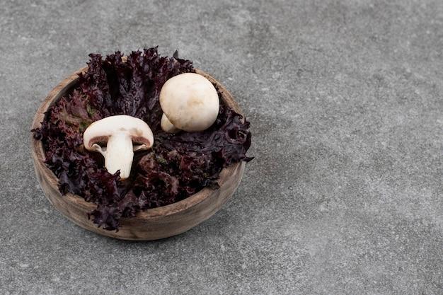 Zamknij świeże grzyby z zielenią w drewnianej misce