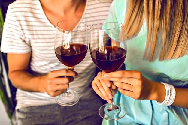 Zamknij szczegóły romantycznego wieczoru ładnej pary pijącej czerwone wino, ciesząc się razem, nowoczesne wnętrze i modne eleganckie ubrania.