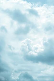 Zamknij teleobiektyw, aby uspokoić białe puszyste bawełniane chmury płynące po niebie.