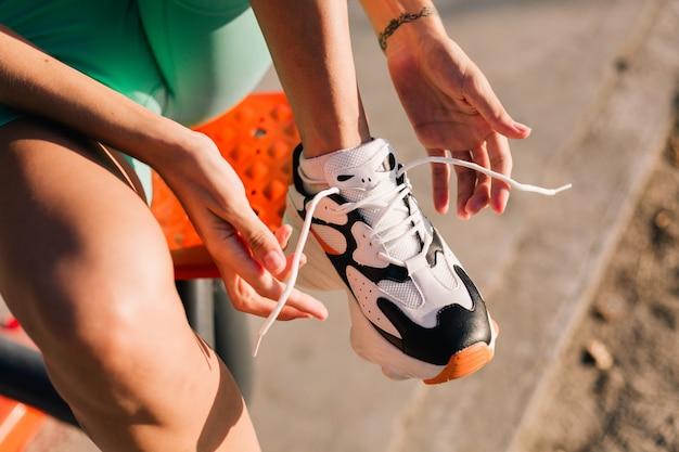 Zamknij ujęcie kobiety wiązanej sznurowadłami na tenisówkach o zachodzie słońca