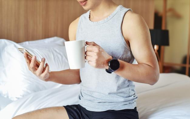 Zamknij uo nastoletniego chłopca w sypialni podczas korzystania ze swojego smartfona i trzymając filiżankę kawy
