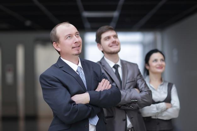 Zamknij up.grupa pewnych siebie ludzi biznesu na tle biura