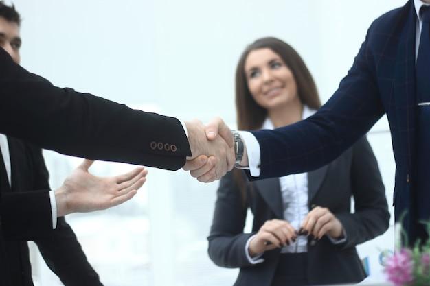 Zamknij up.handshake partnerów biznesowych w tle biura.