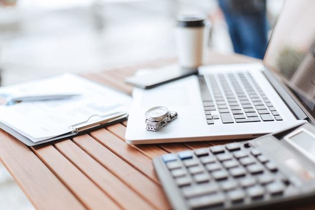 Zamknij up.image laptopa i kalkulatora na stole w kawiarni. zdjęcie z miejscem na kopię.