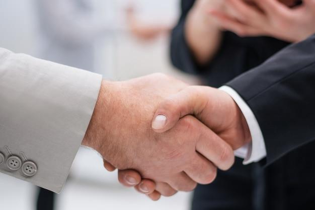 Zamknij up.strong uścisk dłoni ludzi biznesu w biurze. koncepcja partnerstwa