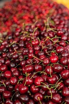 Zamknij upu zdjęcie wielu bordowych, czerwonych wiśni sprzedawanych na rynku. rynek owoców .