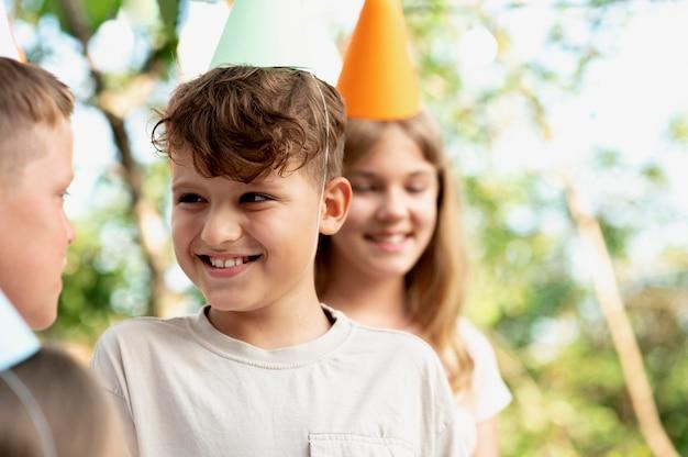 Zamknij uśmiechnięte dzieci w czapkach imprezowych