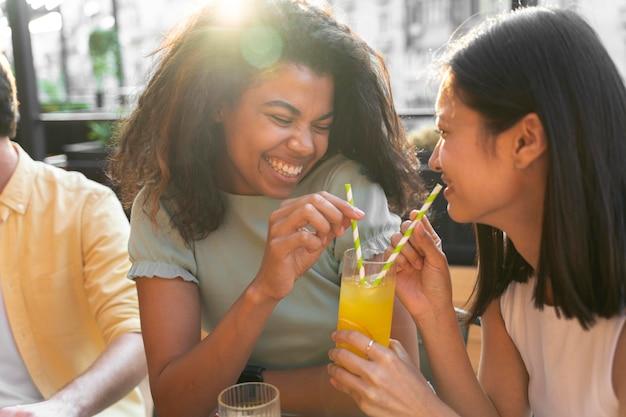 Zamknij uśmiechnięte kobiety z napojem