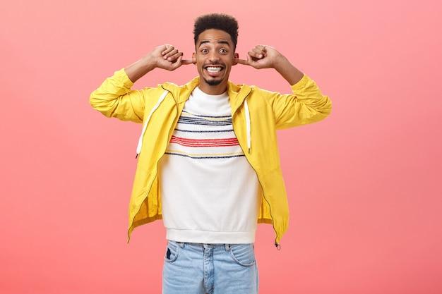 Zamknij uszy, niech będzie głośno portret szczęśliwego, podekscytowanego, przystojnego, stylowego afrykańskiego faceta z brodą w modnym żółto...
