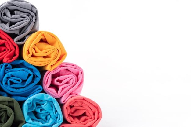 Zamknij w górę kolorowe rolek bawełnianej koszulki wykonane w kształcie piramidy na białym tle.