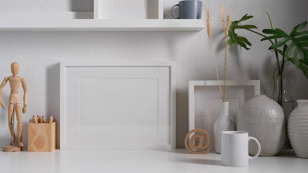 Zamknij widok białego stołu roboczego koncepcji z materiałami eksploatacyjnymi, makietą ramy, dekoracjami i miejscem na kopię
