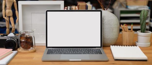 Zamknij widok biurka domowego z laptopem, papeterią, filiżanką kawy, materiałami eksploatacyjnymi i dekoracjami, ścieżką przycinającą.
