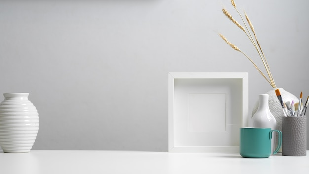 Zamknij widok biurka domowego z miejsca na kopię, makiety ramki, pędzli i dekoracji w białej koncepcji