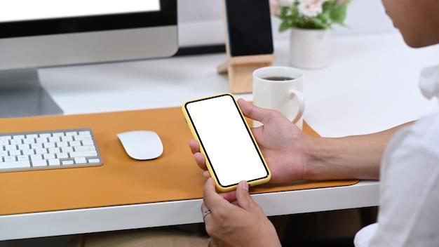 Zamknij widok biznesmen posiadający inteligentny telefon z pustego ekranu na biurku.