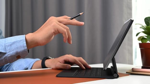 Zamknij widok biznesmen ręka trzyma ołówek i wskazując na komputerze typu tablet
