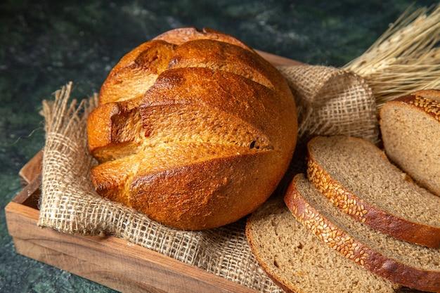 Zamknij widok całego i pokrój świeżego czarnego chleba na ręcznik w brązowym drewnianym pudełku na ciemnej powierzchni mix kolorów