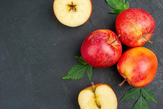 Zamknij widok całych i pokrojonych świeżych czerwonych jabłek i liści na czarnym tle