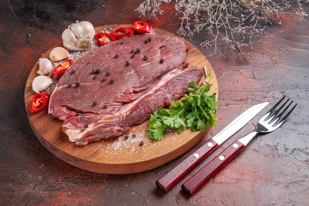 Zamknij widok czerwonego mięsa na drewnianej tacy i czosnku z zielonym pieprzem cytrynowym cebula widelec i nóż na ciemnym tle