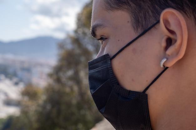 Zamknij widok człowieka za pomocą maski z miasta malaga w tle.