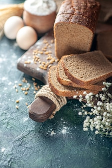 Zamknij widok dietetycznych pszennych czarnego chleba na drewnianej desce do krojenia mąka z jaj kwiatowych w misce na niebieskim tle