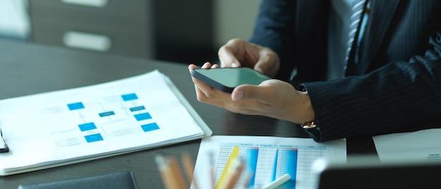 Zamknij widok dłoni biznesmen za pomocą smartfona podczas pracy z informacjami biznesowymi na biurku