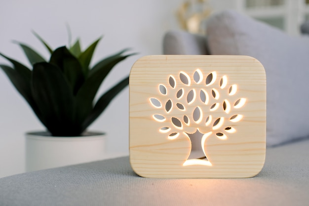 Zamknij widok drewnianej lampki nocnej z obrazem drzewa, na stylowe jasne wnętrze domu, na szarej nowoczesnej sofie