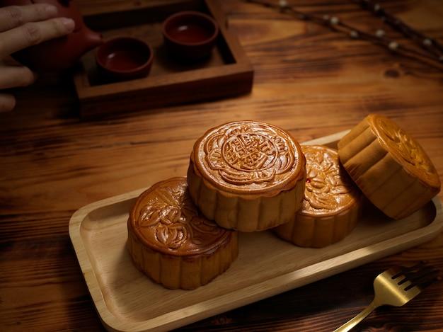 """Zamknij widok drewniany talerz tradycyjnych księżycowych ciast na rustykalnym stole. chińskie znaki na księżycowym cieście oznaczają w języku angielskim """"pięć ziaren i pieczeń wieprzową"""""""