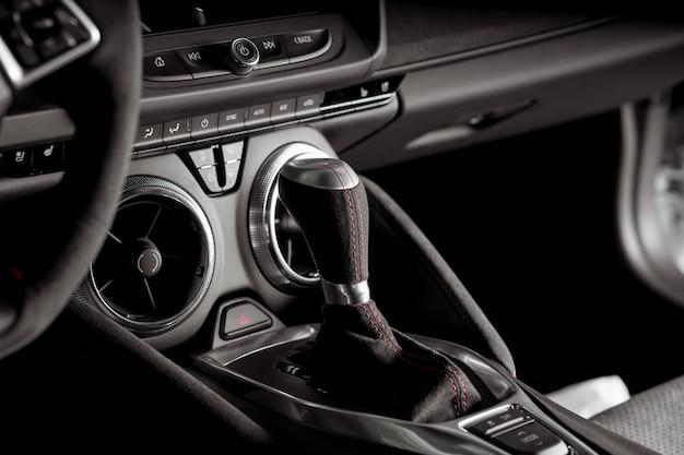 Zamknij widok dźwigni automatycznej skrzyni biegów wewnątrz samochodu sportowego, czarno-białe