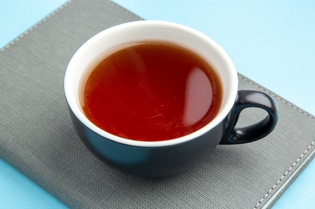 Zamknij widok filiżanki czarnej herbaty na szarym notatniku na niebieskiej powierzchni