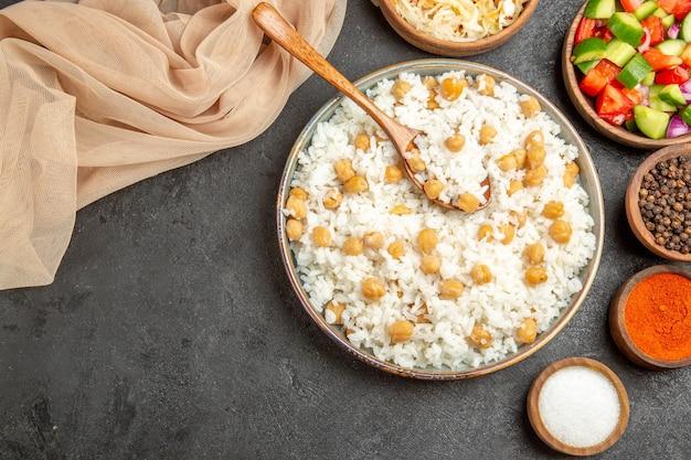 Zamknij widok grochu i ryżu naczynia na obiad z łyżką i ręcznikiem z kiszonej kapusty na ciemnym stole