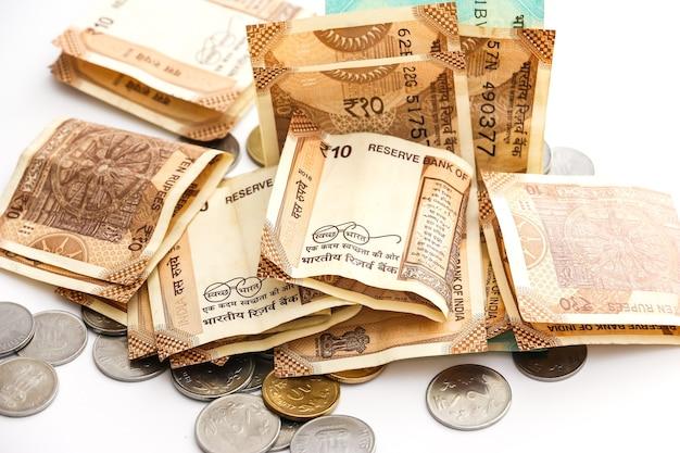 Zamknij widok indyjskich banknotów i monet na białym tle.
