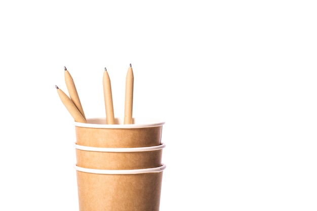Zamknij widok jednorazowych brązowych papierowych kubków z ekologicznymi organicznymi długopisami wielokrotnego użytku na białym tle. ekologia, naturalne materiały biodegradowalne, koncepcja recyklingu. skopiuj miejsce na tekst