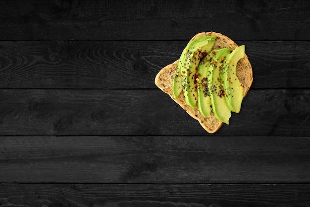 Zamknij widok kanapki z awokado na białym tle na czarnym drewnianym stole.